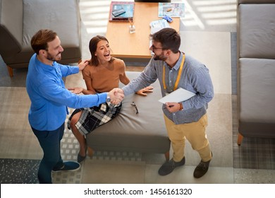 Young couple with salesman in store furniture for the house