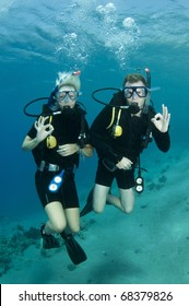 young couple scuba diver and give OK sign in the red sea