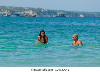 Young couple in sea on surfboards