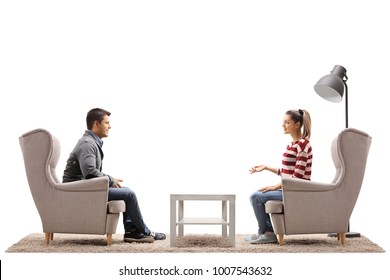 Young couple seated in armchairs having a conversation isolated on white background