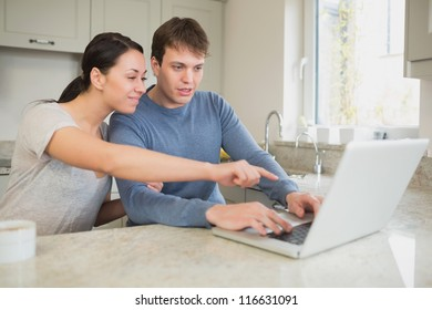 Young couple seeing something interesting on laptop in kitchen