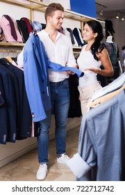 Young couple selecting men's jacket at clothing store