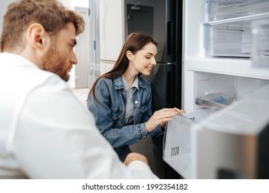 Junge Ehepaare, die einen neuen Kühlschrank im Haushaltsgerätehaus auswählen