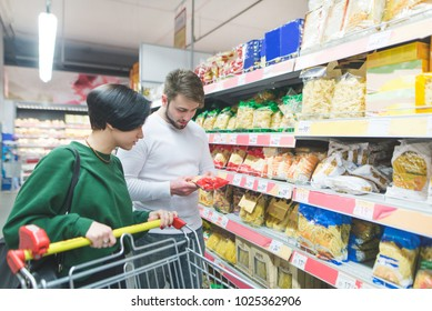 A young couple selects the products in the supermarket. The couple picks up pasta. Family shopping in a supermarket.