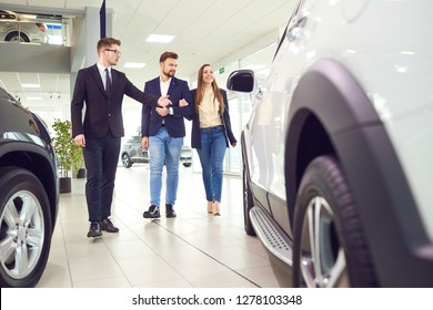 A young couple and the seller choose a car in the showroom