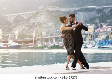 Young couple of sexy beautiful dancers, performing argentine tango dance steps on the dock in the port of Salerno, Italy. Sunset light, vintage retro look.