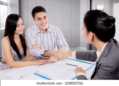 Young couple shaking hand with real estate agent in a meeting