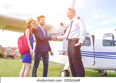 Young couple shaking hands with the pilot of a private plane during their vacation - Caucasian people - people, lifestyle and transportation concept