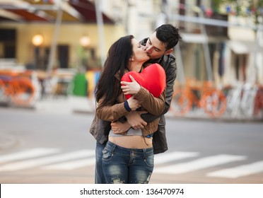 Young couple with shape heart kissing on the street