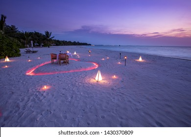 A young couple share a romantic dinner with candles heart shape close the sea sandy beach. Beautiful honeymoon destination, luxury travel, exotic beach dinner at sunset sky with sea background