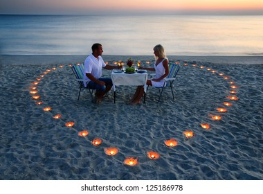 Young couple share a romantic supper with candles heart on the sea sand beach