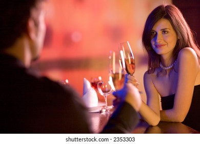 Young couple sharing champagne glasses in restaurant, celebrating or on romantic date. Focus on woman.