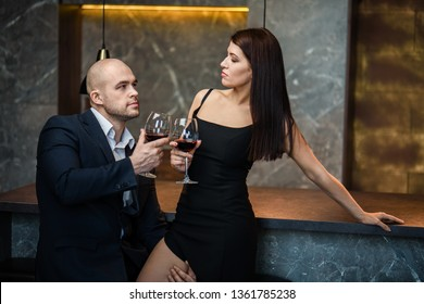 Young couple sharing a glass of red wine in restaurant. A bald man in a black suit and a dark-haired girl in a black dress drink red wine in a restaurant.