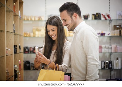 A young couple sharing a laugh while shopping in a cosmetics store.They are buying a perfume.Selective focus
