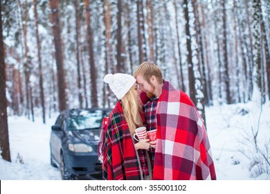 young couple sheltered red plaid holding a hot tea to the car in winter wood