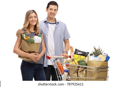 Young couple with shopping bags and a shopping cart filled with groceries isolated on white background