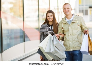 Young couple with shopping bags walking outdoors