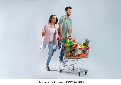 Young couple with shopping cart full of groceries on grey background