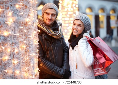 Young couple shopping at christmas fair, smiling happy.