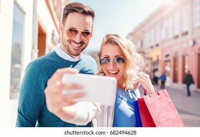 Young couple in shopping. Handsome young couple holding shopping bags on their shoulders while taking a selfie with a mobile phone. Consumerism, fashion, shopping, lifestyle concept