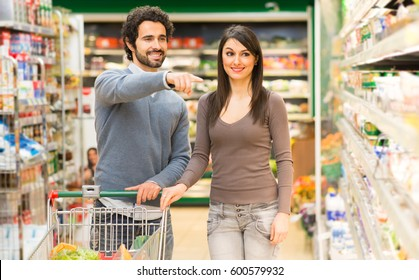 Young couple shopping in a supermarket. The man is pointing his finger at a product