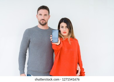 Young couple showing smartphone screen over isolated background with a confident expression on smart face thinking serious