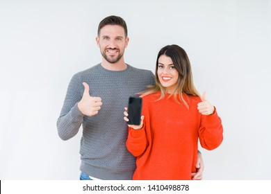 Young couple showing smartphone screen over isolated background happy with big smile doing ok sign, thumb up with fingers, excellent sign