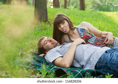 Young couple showing their tongues to photographer on a sunny day outdoors
