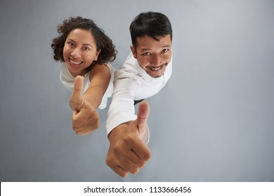 Young couple showing thumb up isolated on gray background above top view