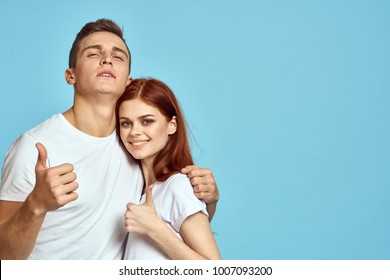 young couple showing thumbs up on blue background