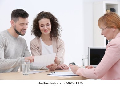 Young couple signing contract at insurance agency office