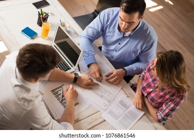 Young couple signing a contract on a meeting with investment agent in the office.