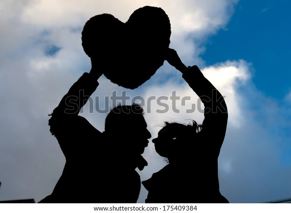 young couple in silhouette holding a love heart shape pillow