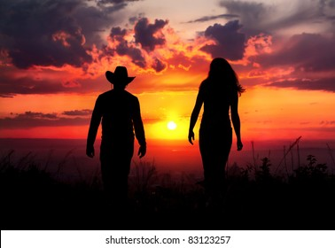 Young couple silhouette walking outdoors at sunset dramatic sky background. Man in cowboy hat and woman nearby