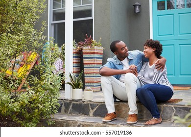 Young couple sit looking at each other outside their house