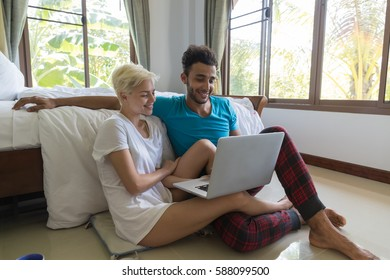 Young Couple Sit Near Bed, Happy Smile Hispanic Man And Woman Using Laptop Computer, Lovers In Bedroom
