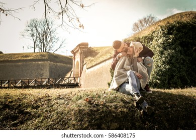 Young couple sit on the grass cuddled.