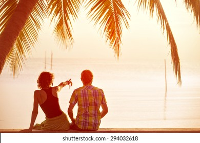 Young couple sit together under a palm tree and looking toward seaside. Girl pointing to something ahead