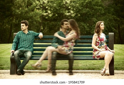 Young couple sits apart on the bench in the park and remembers their love story