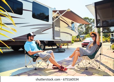 Young couple sits near camping trailer,smiling.Men talks on mobile phone and uses electronic device, woman relax on chair near car and palms.Family spending time together on vacation in rv park