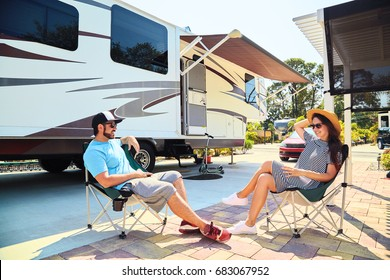 Young couple sits near camping trailer,smiling.Men and woman talking and relaxing on chairs near car and palms.Family spending time together on vacation in rv park