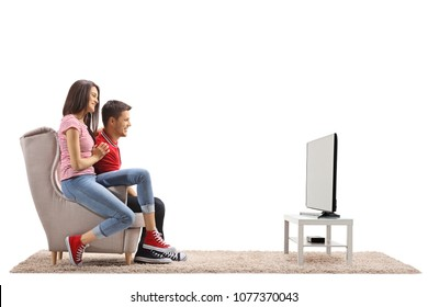 Young couple sitting in an armchair and watching television isolated on white background