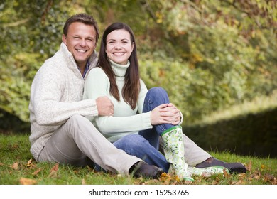 Young couple sitting in autumn woods