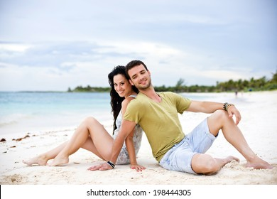 Young couple sitting back to back in a tropical beach
