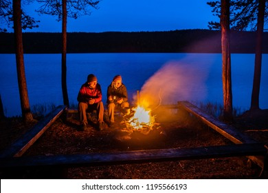 Young couple sitting by the open fire near the lake after sunset, Lapland, Finnland