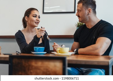 Young couple sitting in cafe at date, drinking coffee and eating dessert.