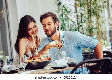 Jovem casal sentado no café e comer porção suculenta de frutas