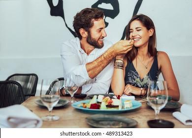 jovem casal sentado em um café e alimentar uns aos outros os bolos suculentos