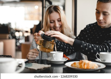 Young couple sitting in cafe. Guy pours green tea to his blonde girlfriend.