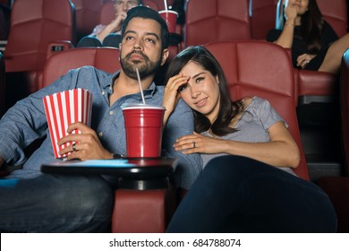Young couple sitting in the cinema theater and watching a scary movie